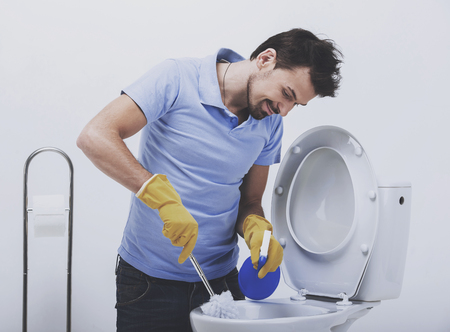 Smiling man is cleaning toilet with brush. Toilet cleaning. Man in working gloves.