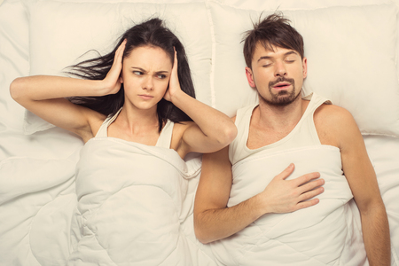 Top view.Angry woman trying fall asleep while man snoring.Awakening of Couple. Stock Photo