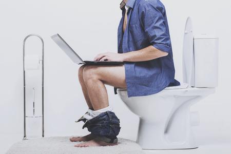Man is working with laptop while sitting on toilet. Sitting in wc with downtrodden pants.