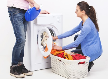 Young couple are doing laundry at home. People near washing machine with basket of linen.