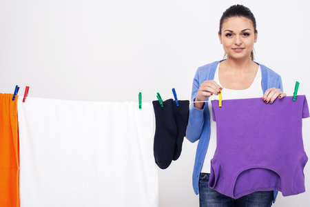 Young woman hangs clothes on dryer for clothes after washing. Womens hands and wet clothes. Post clothes after washing. Stock Photo - 102994072