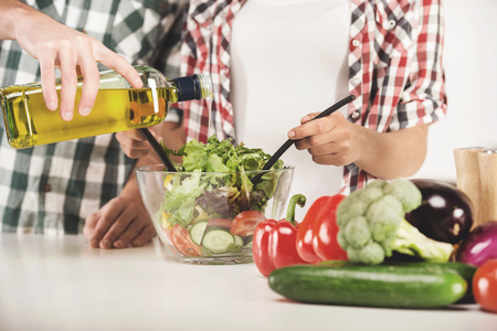 Young couple are preparing salad in kitchen at home. Hand vegetables and oil close up.