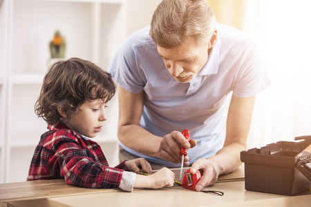 Little baby grandson and his grandfather works with screwdriver. The succession of generations. Stock Photo
