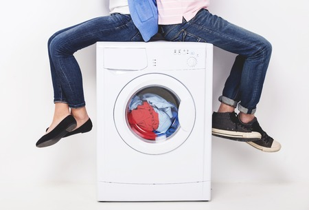 Legs of young couple sitting on washing machine. Wash clothes.