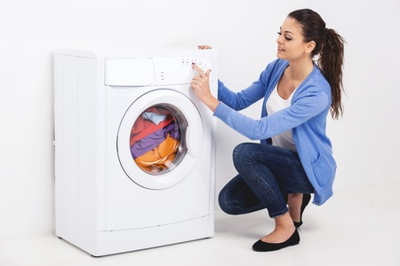 Closeup of young woman pressing button of washing machine on white background.