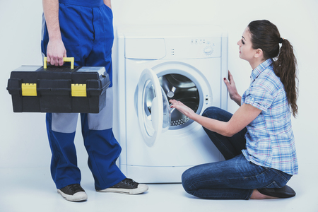 Young housewife and repairman near washing machine. Repair of washing machine.