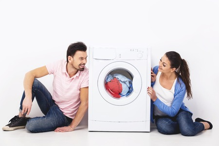 People look at each other sitting near to the washing machine.