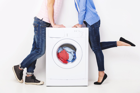 Couple kissing near washing machine. Loving woman and young man in laundry.