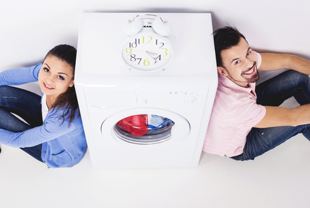 Young couple looking up near washing machine. Alarm clock on washing machine. Top view.
