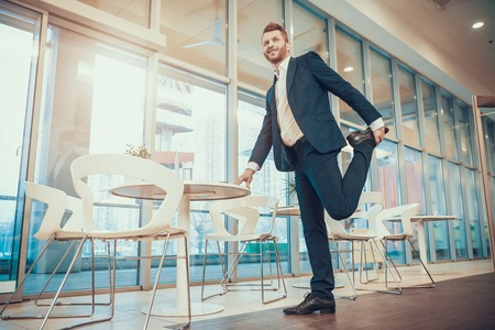 Worker in suit stretching leg at table in office.