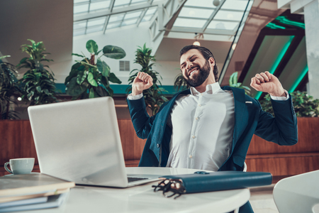 Worker man in suit exercising stretching arms in office.