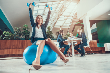 Female worker exercising on fitness ball in office.
