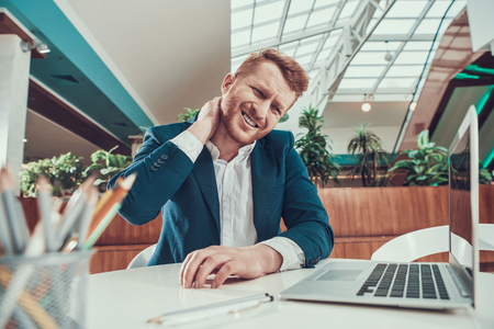 Worker mans in suit neck hurts at desk in office.