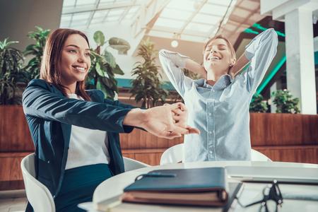 Twee vrouwen die zich uitstrekken bij balie in kantoor. Stockfoto