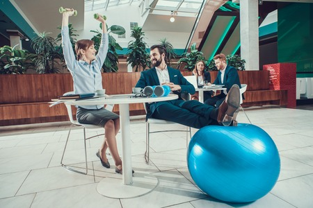 Male and female workers exercising stretching arms in office. Stok Fotoğraf