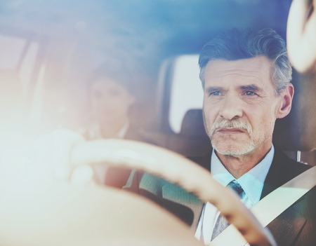 Driver in Luxury Car with Woman on Back Seats. Personal Chauffeur for Businesswoman. Working Professional Chauffeur Concept. Businesswoman Inside Luxury Car. Successful Business Concepts.