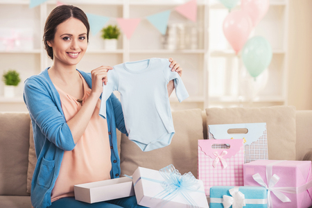 Smiling Pregnant Woman with Blue Baby Romper. Happy Pregnant Mother Holding Romper in Bedroom at Home. Pregnancy and Motherhood Concept. Young Mother Expecting Baby Concept. Maternity Concept.