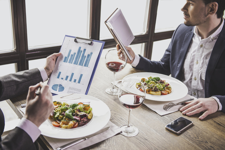 Two Businessmen Have Business Lunch with Glasses of Red Wine in Restaurant. Business Concept. Discussion of Financial Successes at Meeting in Modern Cafe. Successful Partnership Concept. Archivio Fotografico