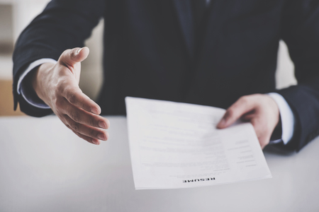 Close up. Young Businessman Taking Resume in Office. Professional HR Manager Sitting in Office and Takes Interview From Employee. Employment and Job Interview Concept. Work Achievement Concept. Stock Photo