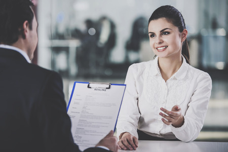Young Businessman Taking Resume from Woman in Office. Professional HR Manager Sitting in Office and Takes Interview From Employee. Employment and Job Interview Concept. Work Achievement Concept.