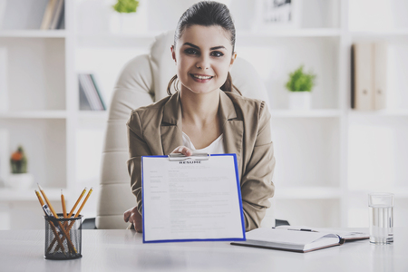 Young Smiling Businesswoman Taking Resume in Office. Professional HR Manager Sitting in Office and Takes Interview From Employee. Employment and Job Interview Concept. Work Achievement Concept.