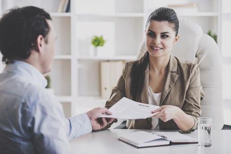 Young Smiling Businesswoman Interviewing Employee. Professional HR Manager Sitting in Office and Takes Interview From Employee. Employment and Job Interview Concept. Work Achievement Concept. Stock Photo