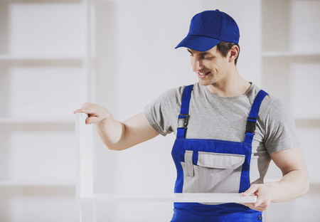 Young Worker Installing Furniture in New Home. Repair and Installation in House. Creating Style for New Place of Residence. Repair in Apartment Concept. Safety of Work in Production and Construction. Фото со стока