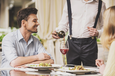 Smiling Young Couple Dating in Restaurant and Drinking Red Wine. Romantic Relationship. Love and Relationship Concepts. Relationship between Two People. Date on Saint Valentines Day.