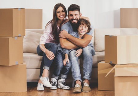 Smiling Family Moving to New Place and Sits on Sofa near Carton Boxes. Moving to New House. Relocation to New Place Concept. Boxes Full of Household Things. Starting Life on New Place. Stock Photo