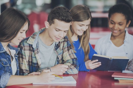 Group of Teenagers Sitting at Table in Cafe and Doing Homework. Education and Study Concept. Homework Help Concept. Friendship and Relationship between Teenagers. Writing Homework.