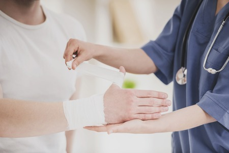 Close up. Doctor in Blue Uniform with Stethoscope Comforting Hand of Patient in Hospital. Traumatology Medical Devices. Medical Treatment in Clinic and Healthcare Professional Concept.