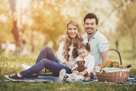 Happy Young Mother and Father with Daughter on Family Picnic on Green Grass in Park on Sunny Summer Day. Happy Family and Healthy Lifestyle Concepts. Fun Outside in Summer Concept.