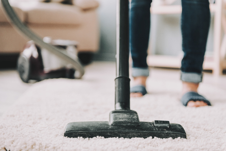 Close up. Woman in Jeans Cleans Carpet with Vacuum Cleaner. Professional Janitor Vacuuming White Carpet. Young Maid Use Vacuum Cleaner. Room Cleaning Concept. Home Routine Concept.
