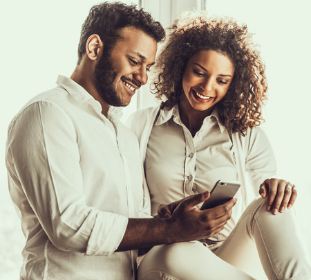 Two Young Smiling Pakistani People in White Clothes Watching into Smarthpone. Arabic Man Holding Cell Phone in Hand. Young Couple Using Gadget. Connectioan and Communication Concept.
