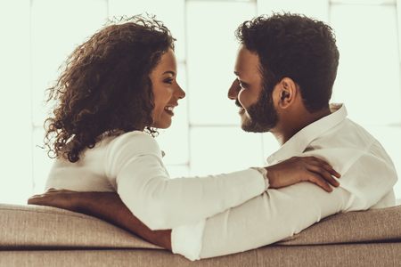 Young Pakistani Couple in White Clothes Sitting on Gray Sofa and Hugging. Arabic Woman and Man. Young Couple Relaxing Indoor. Romantic Relationship Concepts. Romantic Relax at Home.