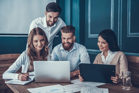 Young Businesspeople Working with Laptop in Modern Office. Office Workers at Work. Communication and Discussion at Work Concepts. Business Concept. Businessman and Businesswoman Concepts.