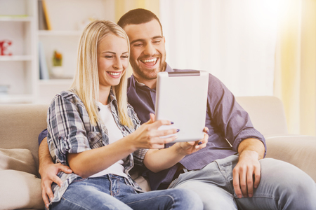 Happy Young Couple Watching into Tablet at Home. Romantic Relationship between People Concept. Date on Saint Valentines Day. Idyll of Young Couple. Love Concept. Romantic Date Concept.