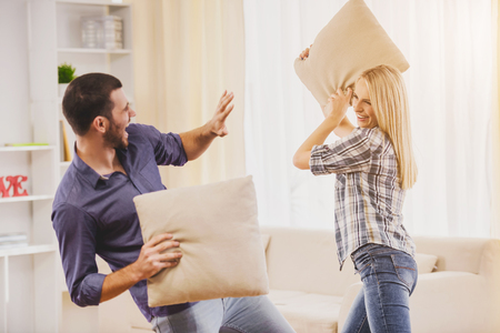 Young Couple Having Pillow Fight in Bedroom at Home. Romantic Relationship between People Concept. Date on Saint Valentines Day. Idyll of Young Couple. Love Concept. Romantic Date Concept. 写真素材