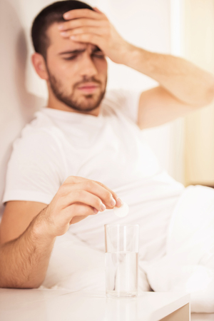 Man Takes Pill from Headache Lying in White Bed. Taking Care of Migraine with Soluble Tablets. Resting in White Bedroom. Glass with Water. Healthcare and Medical Treatment Concept. Фото со стока