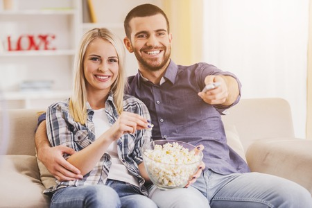 Happy Young Couple Eating Popcorn at Home. Romantic Relationship between People Concept. Date on Saint Valentines Day. Idyll of Young Couple. Love Concepts. Romantic Date Concept.