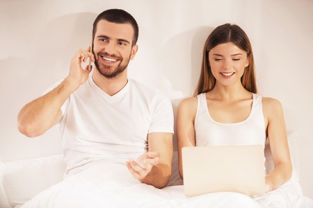 Young Couple in Bed with Smartphone and Laptop. Simple interior of Bedroom. Family problem. Using Gadgets in Bed. Ignoring Problem. Family Life Concept. Relationship between People Concept.