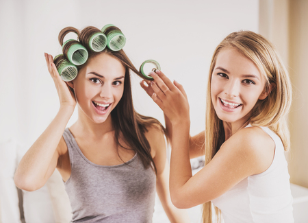 Beautiful Smiling Girl Helps Girlfriend to Curl Hair. Joyful Chatting with Friends in Morning Concept. Modern Fashion Style in Bedroom. Modern Fashion Concept. Female Friendship Concept.