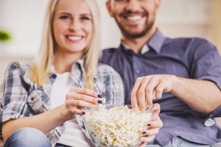 Close up. Happy Couple Eating Popcorn at Home. Romantic Relationship between People Concept. Date on Saint Valentines Day. Idyll of Young Couple. Love Concept. Romantic Date Concept. 写真素材