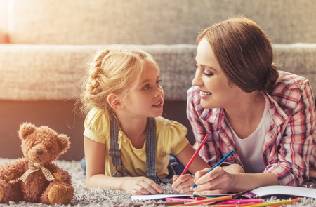 Cute Little Girl and Her Beautiful Mother Drawing. Mom and Happy Daughter Looking at Each Other. Family Smiling While Lying on Floor at Sweet Home. Family Happiness Activitiy Concept. Imagens - 104540163