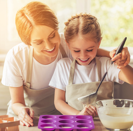 Beautiful Woman and Her Cute Little Daughter in Aprons Smiling. Mom with Child Filling Muffin Cases. Loving Mother and Pretty Daughter Baking. Happy Mom Helps Her Lovely Daughter Cook.