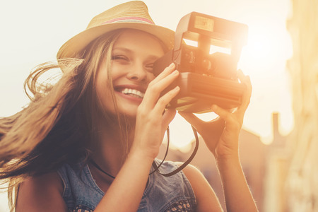 Beautiful Stylish Young Girl in Casual Clothes and Hat. Girl Making Photos with Camera and Smiling While Walking Outdoors. Professional Sweet Photographer Enjoys Magic Moment. Sunny Evening.