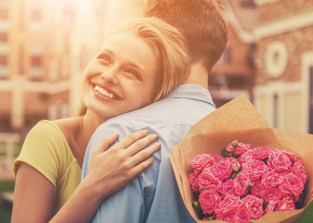 Beautiful Young Couple on Wonderful First Date. Attractive Cute Girl Hugging Her Boyfriend Holding Flowers and Smiling. Large Bouquet of Pink Roses. Lovers Boy with Girl Enjoy Moment.