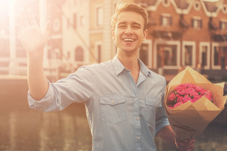 Handsome Guy in Casual Clothes Keeping Flowers and Smiling While Waiting for His Girlfriend. Beautiful Young Guy. Man Waves His Hand to His Girlfriend on Camera. Long Awaited Meeting with Beloved. Banque d'images - 104540333