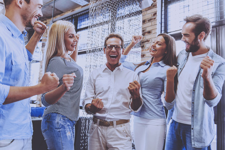 Beautiful Business Team in Casual Wear Holding Hands in Fists and Smiling. Successful Smart Strong Business Team. Feeling Success Concept. People Get Maximum Pleasure from Working Together.