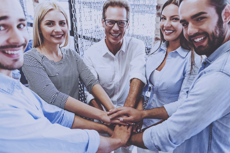 Beautiful Business Team in Casual Wear Holding Hands Together. People Looking at Camera and Smiling. Strong Business Team. Feeling Success Concept. People Get Maximum Pleasure from Working Together.